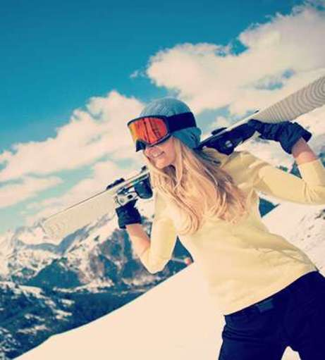 Woman in ski goggles in a yellow long sleeve top in the mountains. Discover Andorra Hen Pa