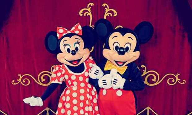 Minnie Mouse and Mickey Mouse with arms linked in front of a gold embellished curtain. Discover Disneyland Paris Hen Party ideas below: